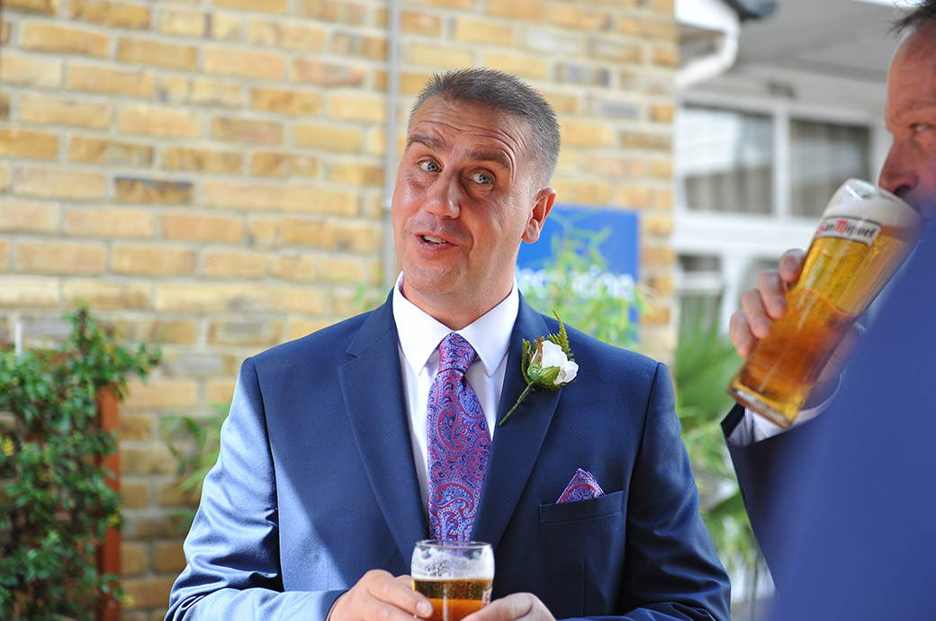 Groom in conversation with a pint in hand at Surrey venue Great Western Ship Hotel Weybridge outside The Thames Suite in the courtyard