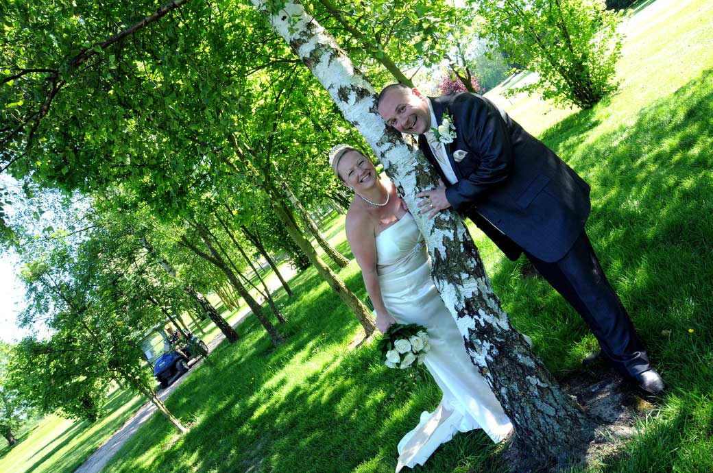 A happy Bride and Groom wedding picture taken as they have fun in the trees off the fairways at a bright and sunny Shirley Park Golf Club