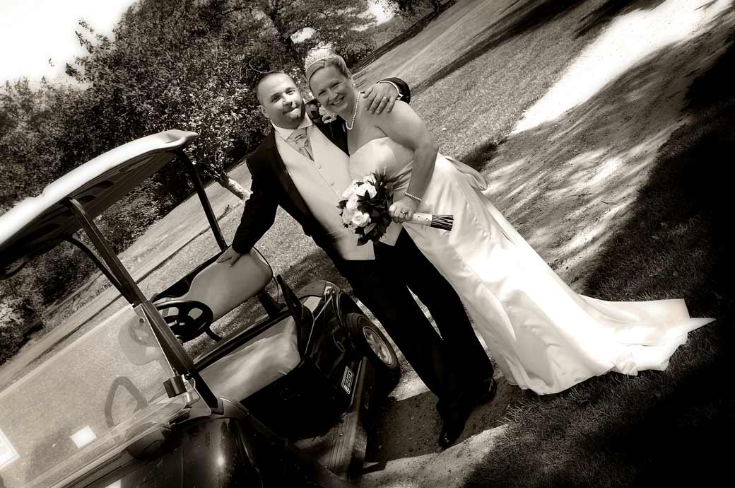 A proud Groom holds his Bride by a golf buggy wedding picture captured by Surrey lane wedding photographer at Shirley Park Golf Club