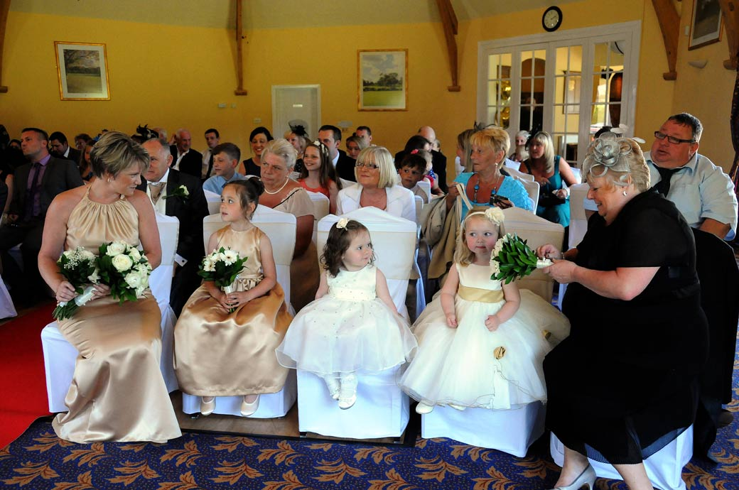 A lovely wedding picture of little cute Bridesmaids sitting on the adult sized chairs during a wedding ceremony at Shirley Park Golf Club