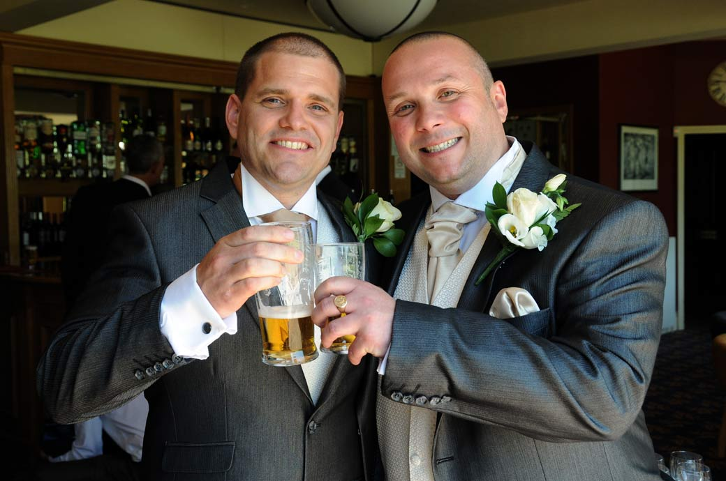Smiling Groom and Best Man take a pre-wedding ceremony pint wedding photo taken in the lounge bar at Shirley Park Golf Club Croydon