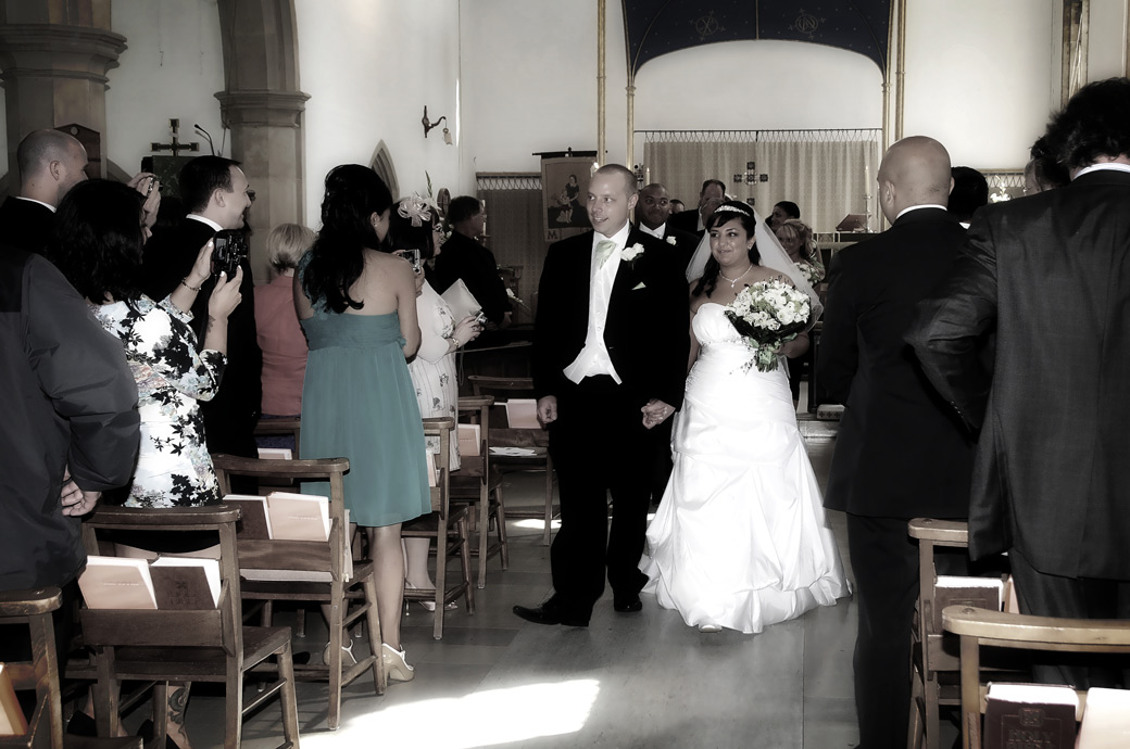 An excited smiling married couple walking down the aisle wedding photo taken at St. John the Evangelist Church, Old Coulsdon an ancient wedding venue in Surrey