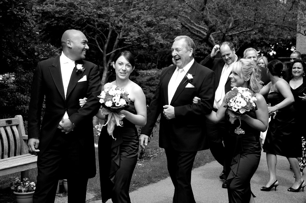 Wedding guests laughing as they share a joke in this fun wedding photograph taken at St. John the Evangelist Church, Old Coulsdon an ancient Surrey wedding venue