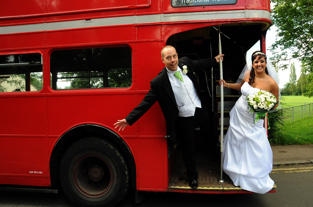 Bride and Groom leaning out of a double decker bus wedding photograph as they leave the Surrey wedding venue St. John the Evangelist Church, Old Coulsdon