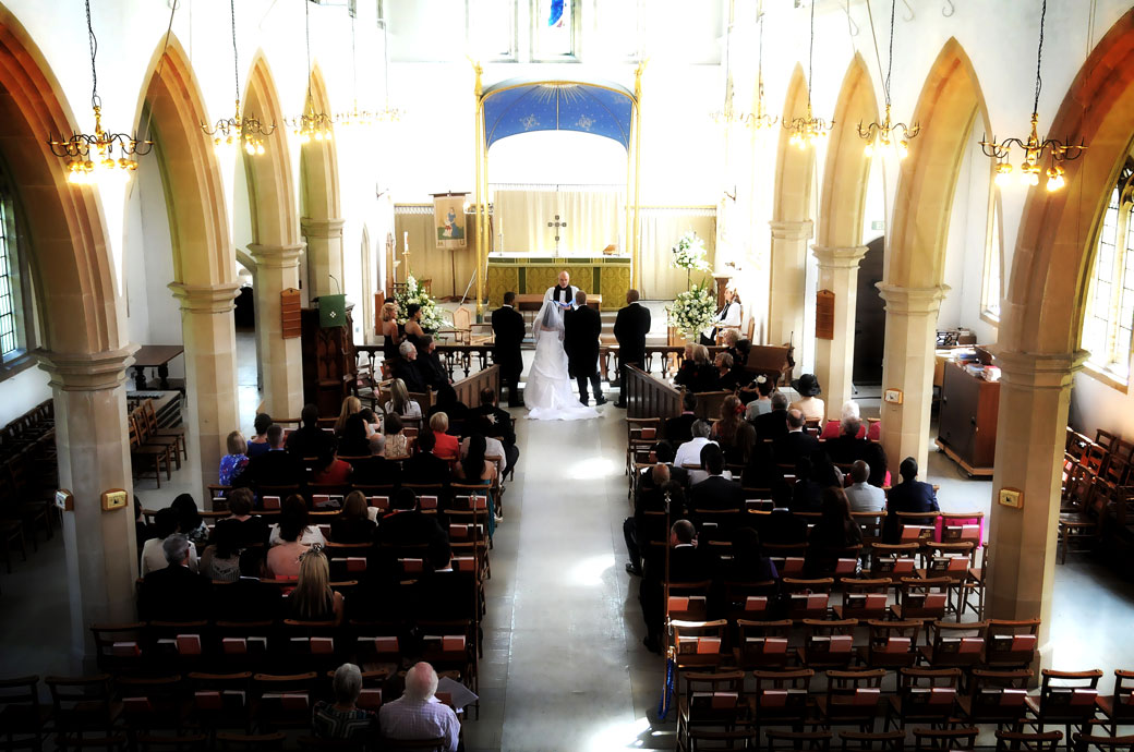 Bride and Groom stand before the vicar in this balcony wedding picture captured at St. John the Evangelist Church, Old Coulsdon an 11th century Surrey wedding venue