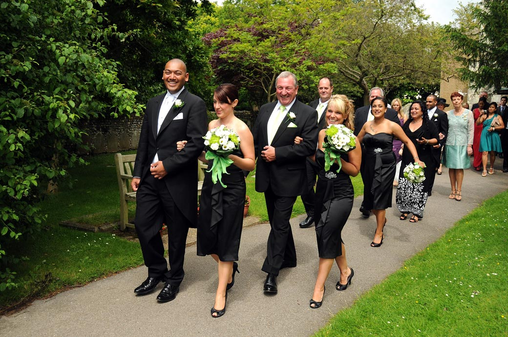 Happy wedding guests walk down the path after the newly-weds in this relaxed wedding photo taken at St. John the Evangelist Church, Old Coulsdon in Surrey