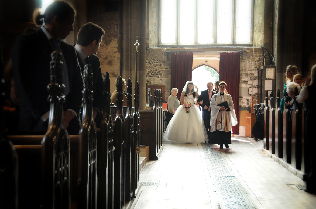 Atmospheric wedding picture of the Bride Father and Vicar walking down the aisle of St Mary's Church Beddington by Surrey Lane wedding photography