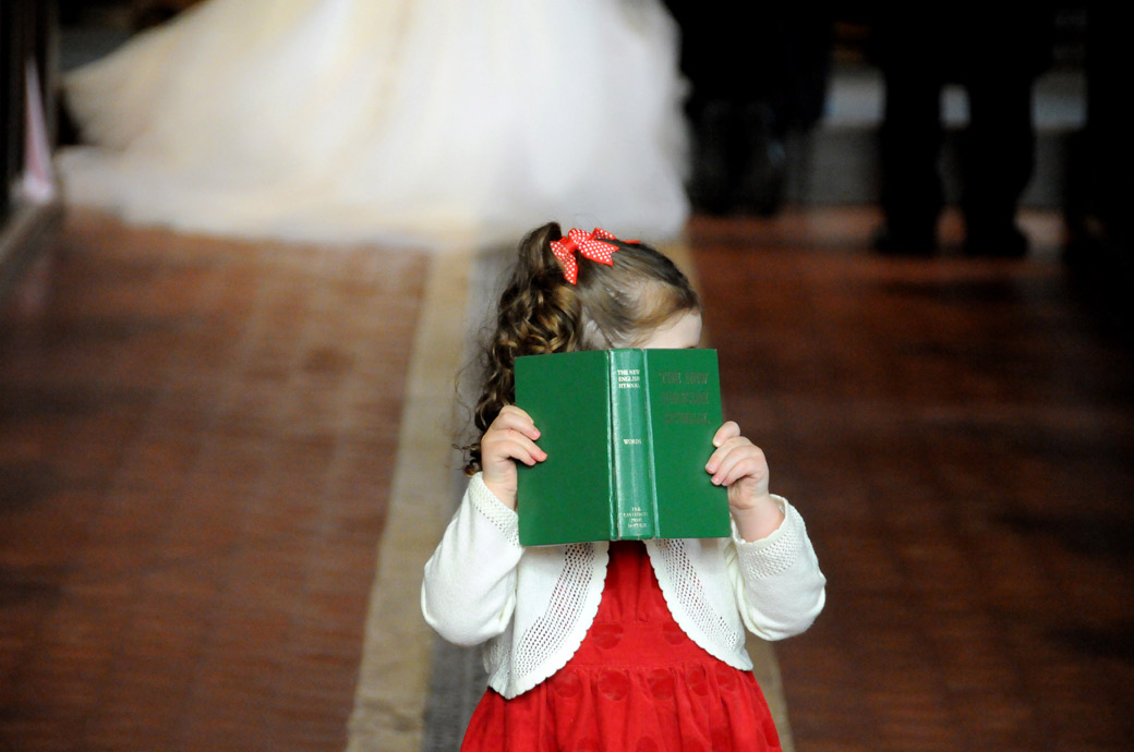 Funny wedding picture of a child hiding behind a bible in the aisle during the wedding ceremony captured at Surrey wedding venue St Mary's Church Beddington