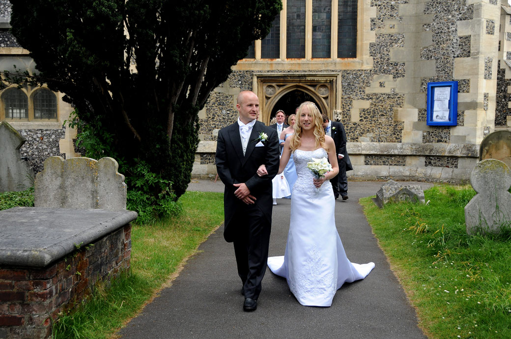 Lovely wedding photo of the newly-weds walking down the path to the lychgate St Mary's Church Beddington an historic Surrey wedding venue