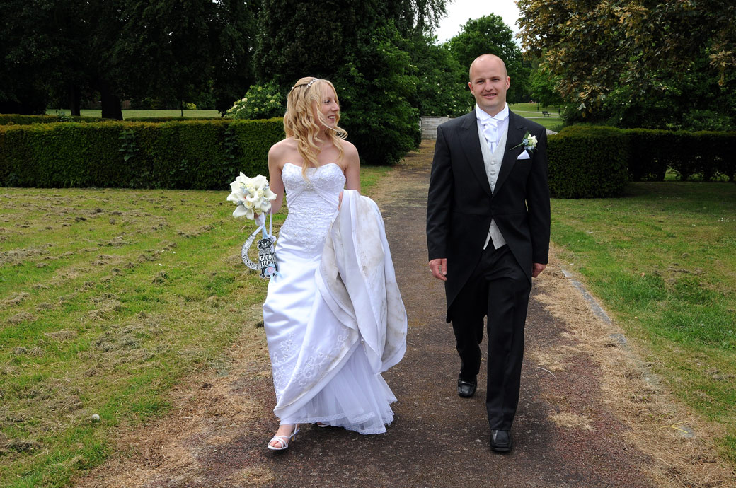 A happy relaxed Bride and Groom taking a walk opposite the Surrey wedding venue of St Mary's Church Beddington Surrey