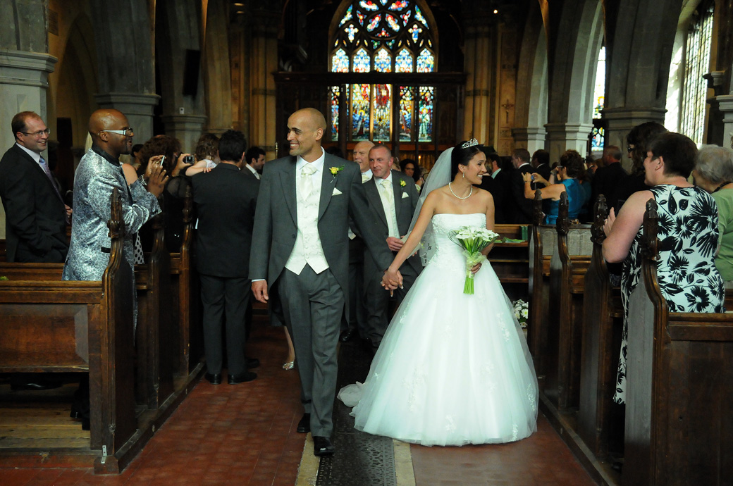 Happy smiling couple as they walk down the aisle wedding photograph captured by Surrey lane wedding photographers at St Mary's Church Beddington