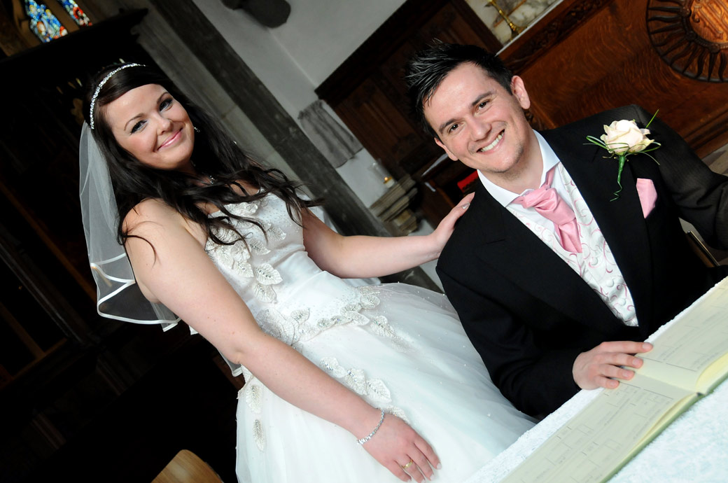 A wedding photograph of a beaming happy newly-wed couple as they pose by the register taken at Surrey wedding venue St Mary's Church Beddington