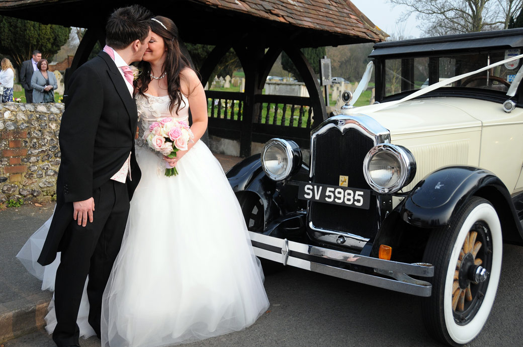 An intimate Bride and Groom moment wedding picture captured in front of the wedding car captured at St Mary's Church Beddington by Surrey Lane weddings