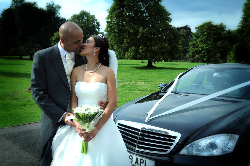 Romantic newly-weds kiss in front of the Bridal car wedding picture captured by Surrey lane wedding photography at St Mary's Church Beddington