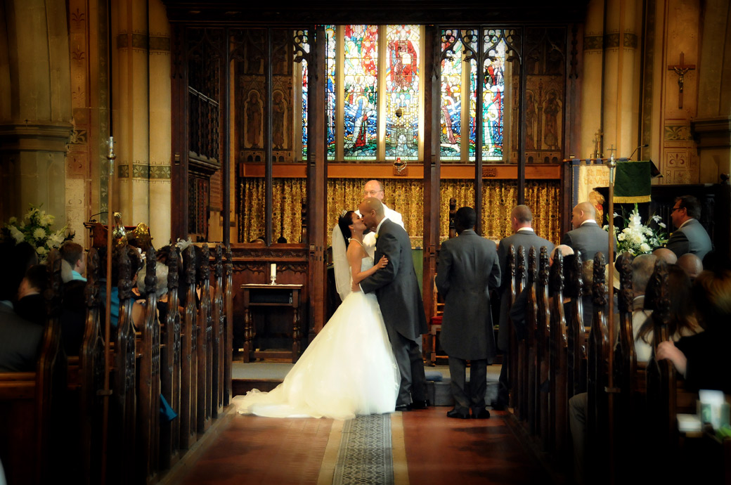 Atmospheric newly-wed's romantic and passionate kiss wedding picture captured at St Mary's Church Beddington by Surrey Lane wedding photography