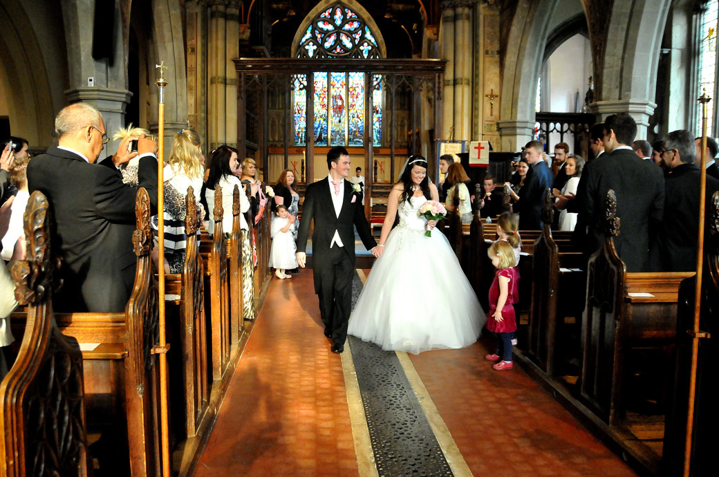 Radiant happy couple walk down the aisle all smiles wedding photo captured by Surrey Lane wedding photography ar St Mary's Church Beddington