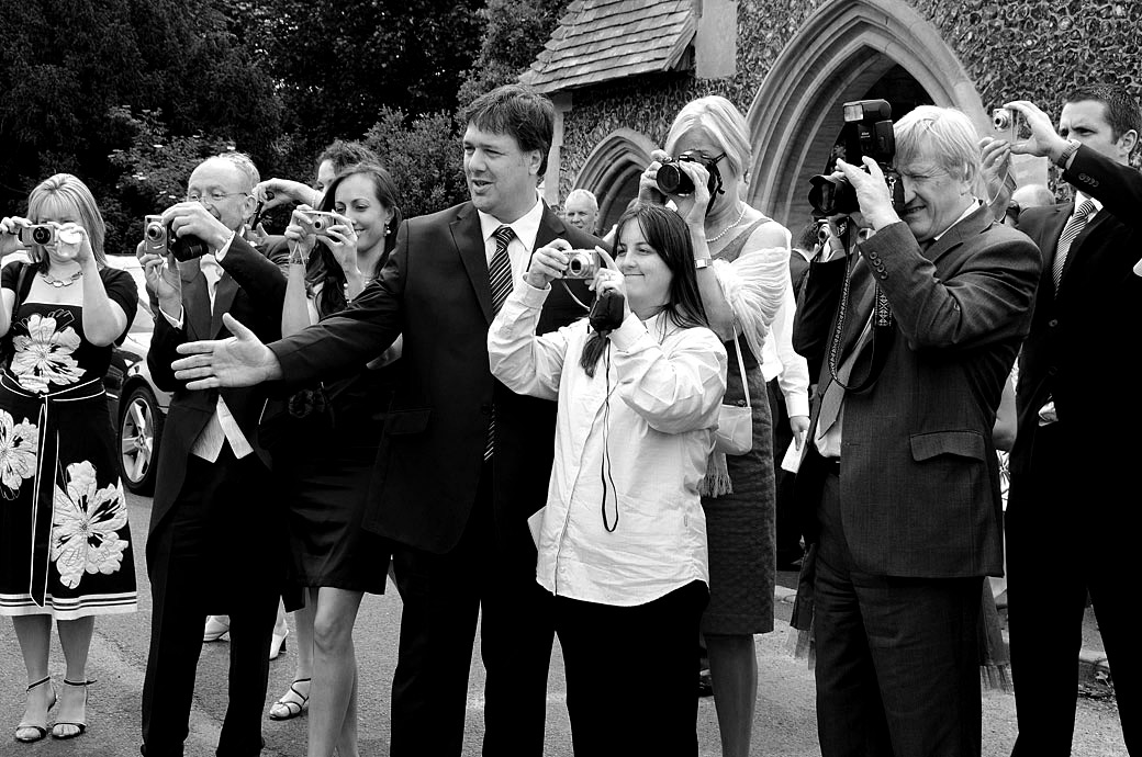Wedding guests with their camera's out wedding photograph captured at St Mary's Church Beddington by Surrey Lane wedding photography