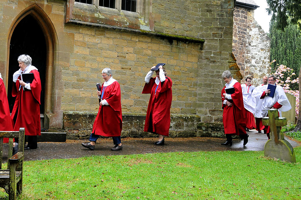 A wedding picture of the choir in their red robes avoiding the rain on their way to St Nicolas Church in Cranleigh a picturesque Surrey wedding venue