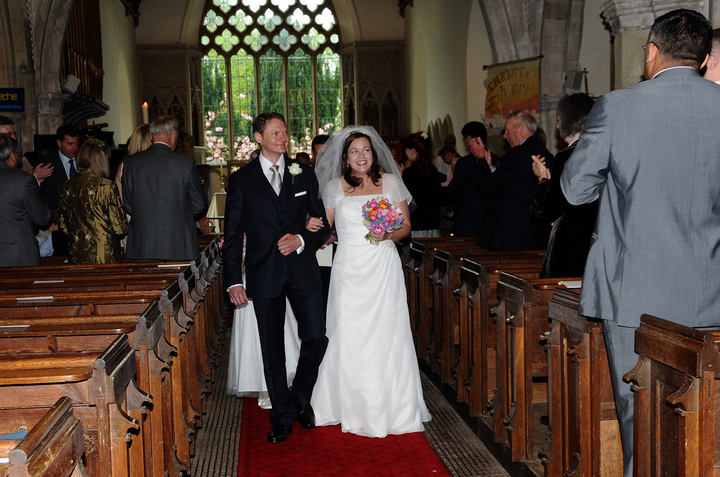A joyful Bride and Groom walk arm in arm down the aisle as man and wife at St Nicolas Cranleigh a picturesque and ancient Surrey wedding venue