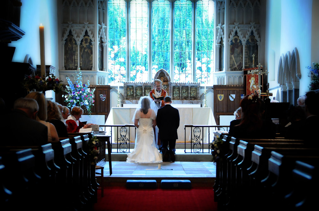A beautifully calming and atmospheric wedding photograph of the Bride and Groom kneeling before the ancient chancel at St Nicolas Church Cranleigh