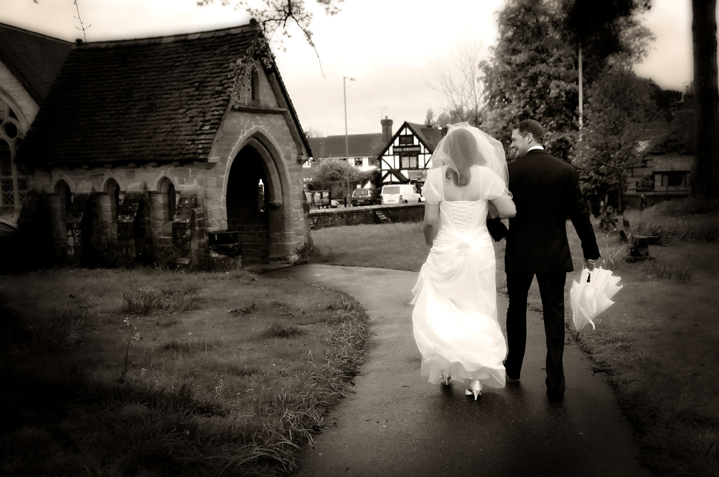 Romantic Bride and Groom walking towards the porch and lych gate wedding photo taken at Surrey wedding venue  St Nicolas Church Cranleigh