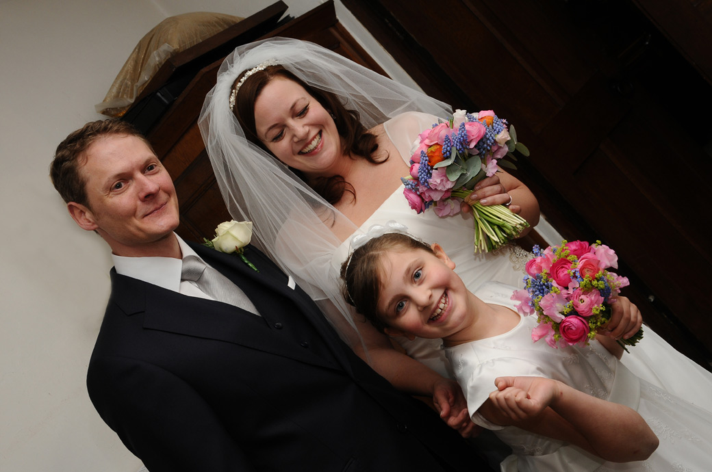 Smiles and pretty colourful bouquets wedding photo captured at St Nicolas Church Cranleigh by Surrey Lane wedding photography