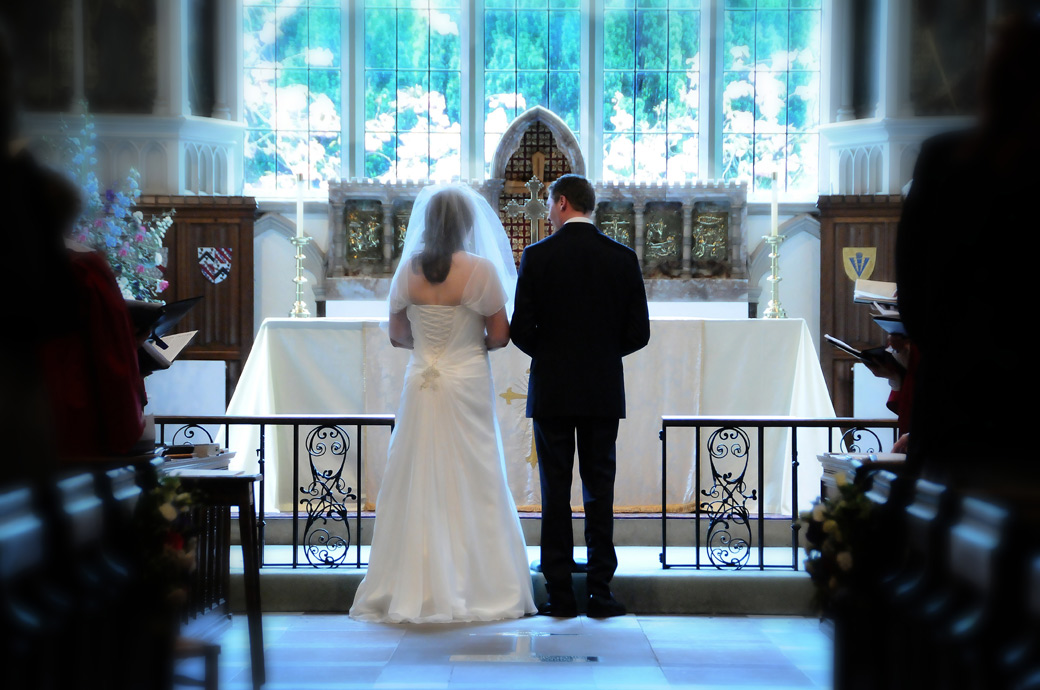 A beautiful atmospheric wedding picture of the Newly-weds standing before the chancel at St Nicolas Cranleigh a fine Surrey wedding venue Church