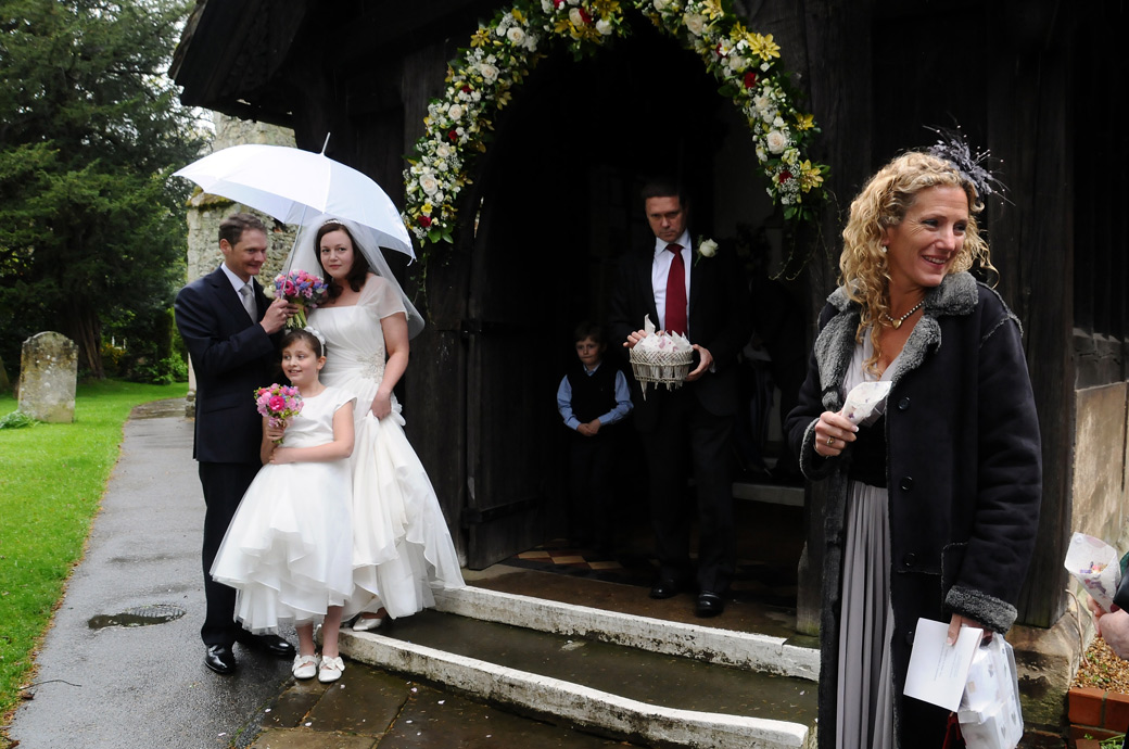 A lovely sweet wedding picture of the Bride Groom and Bridesmaid under the umbrella at St Nicolas Cranleigh Surrey waiting for the confetti