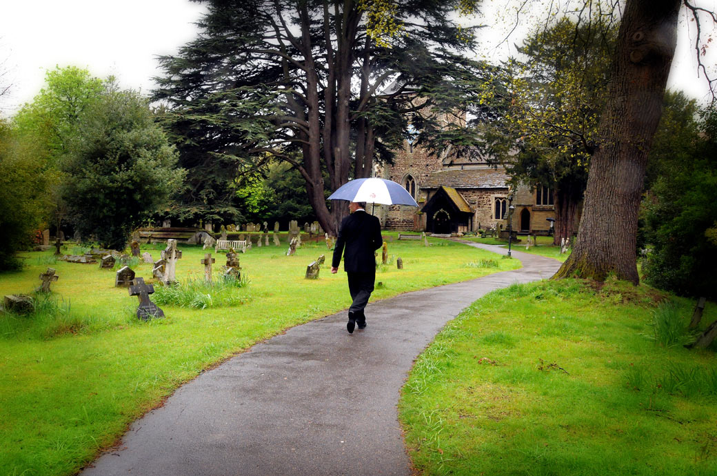 Wedding photograph of the Best Man walking under his umbrella on the path towards the ancient Surrey wedding venue of St Nicolas Church Cranleigh