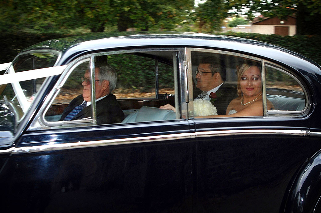 An excited Bride looks through the window in this wedding picture captured in the wedding car for Surrey wedding venue Stanhill Court Hotel