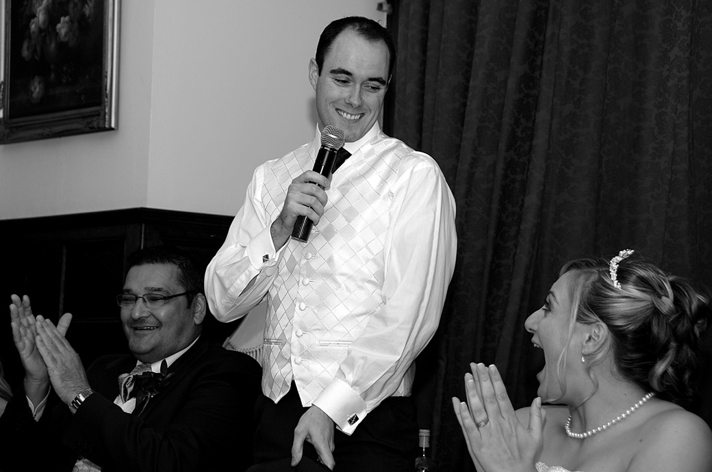 Groom smiles down to his Bride as he makes her laugh during the speeches in this wedding photograph taken at Surrey wedding venue Stanhill Court Hotel, Horley