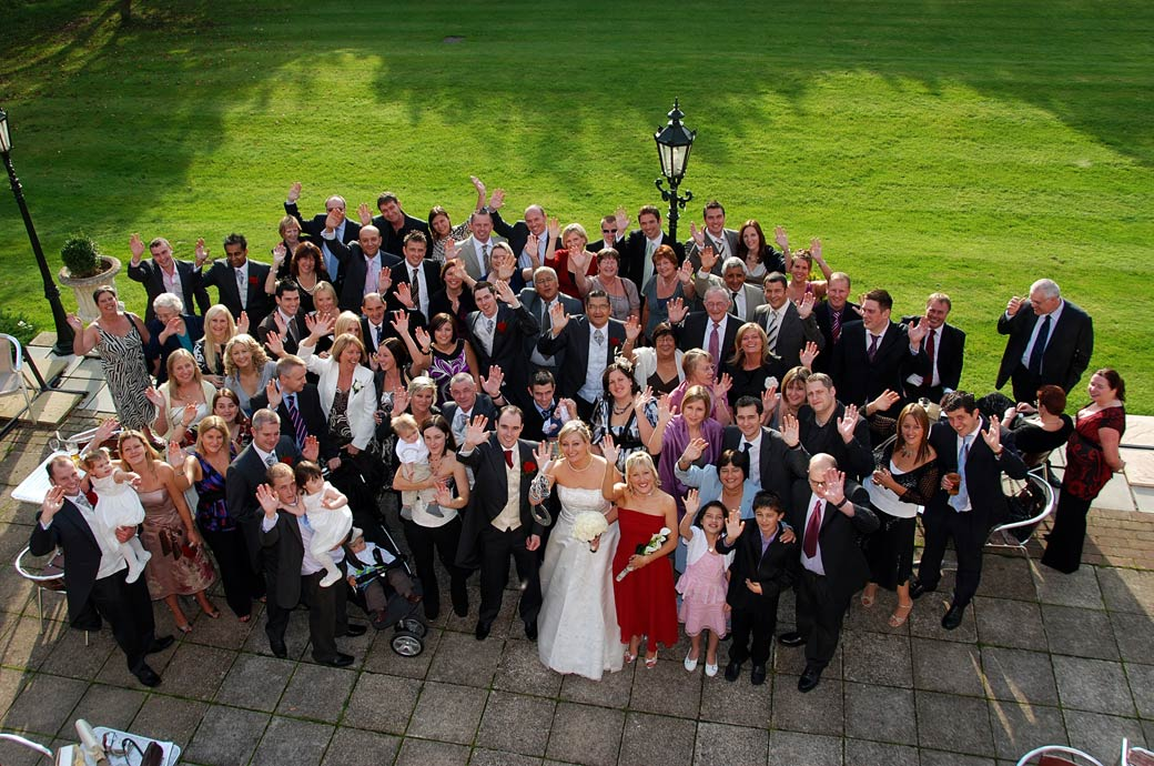 Guests waving on the terrace for this everyone at the wedding picture taken from the upper windows of Stanhill Court Hotel a fine Surrey wedding venue