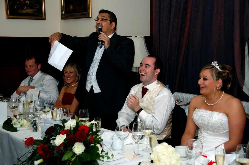Father of the Bride tells a joke and makes everyone laugh in this fun speeches wedding photo taken at Stanhill Court Hotel by Surrey Lane wedding photographers