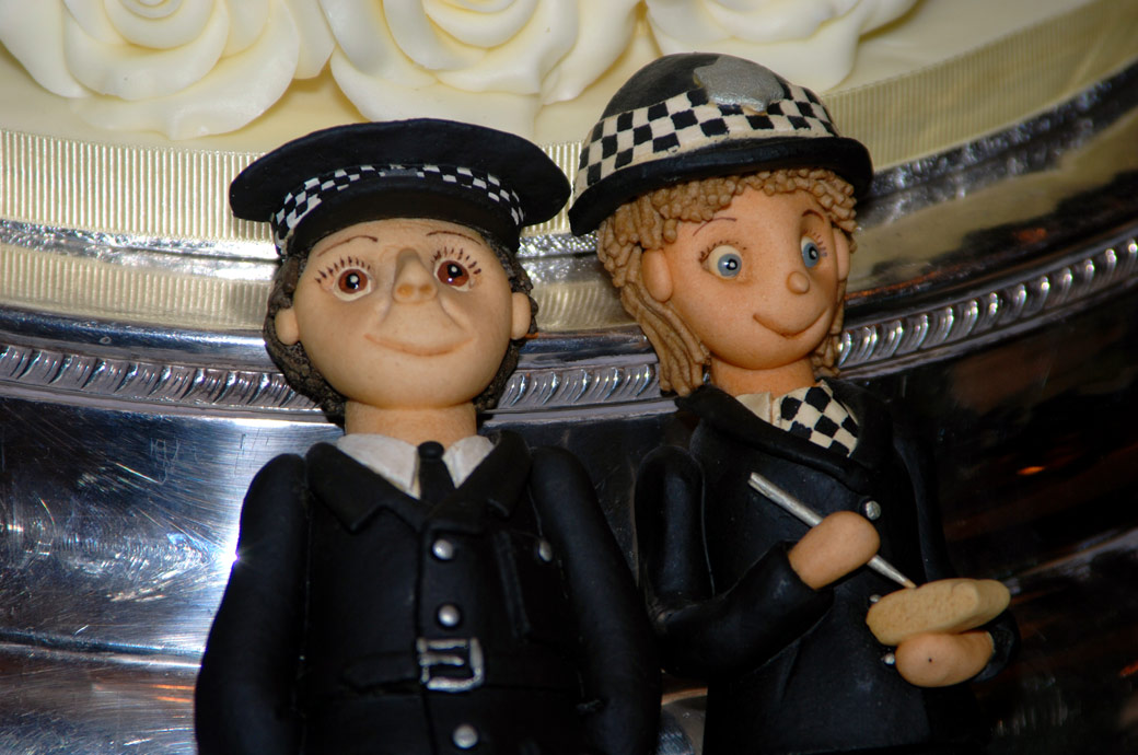 A fun Bobbies on the Beat figurine cake topper wedding photo taken by Surrey Lane wedding photography at Surrey wedding venue Stanhill Court Hotel, Horley