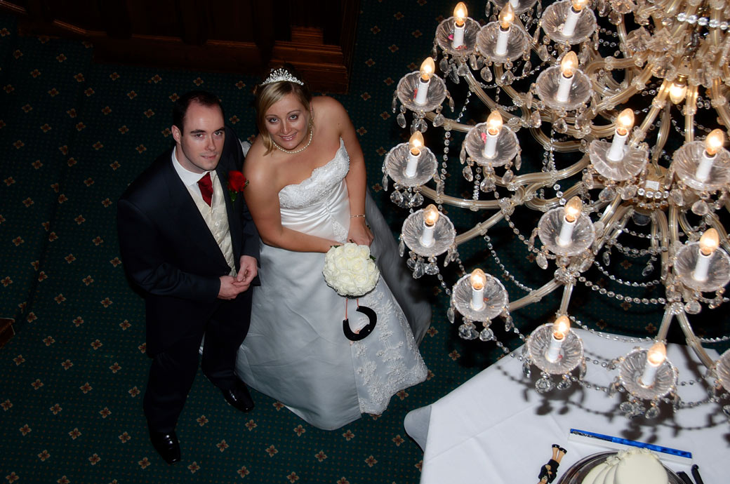 Bride and Groom look up past the chandeliers in this wedding photo taken from the top of the main staircase at Stanhill Court Hotel a great Surrey wedding venue