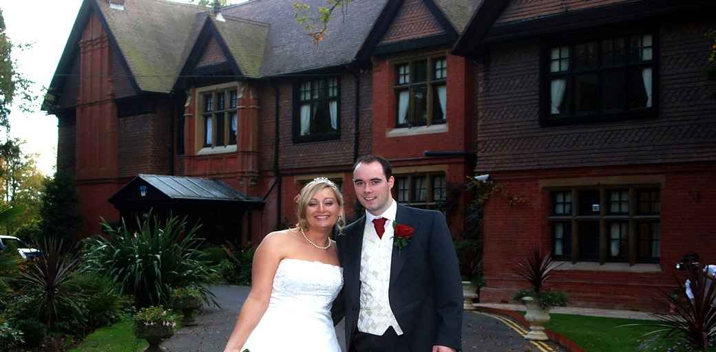 Bride and Groom smiling in this wedding picture taken outside the large Victorian Surrey wedding venue Stanhill Court Hotel in Horley by Surrey Lane wedding photography
