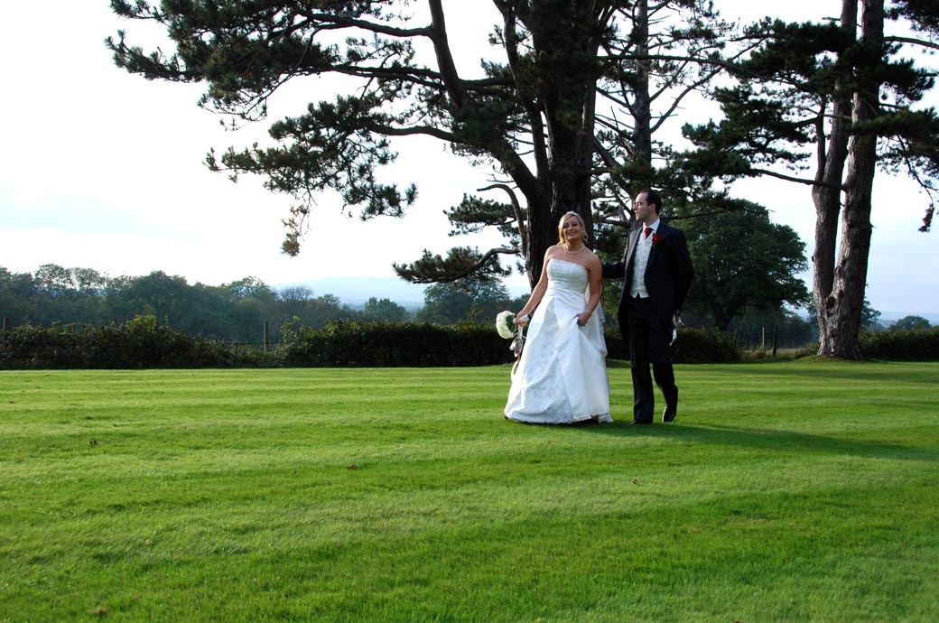 The happy Bride and Groom walk together over the lawn in this relaxed wedding picture by Surrey Lane wedding photography at  Stanhill Court Hotel