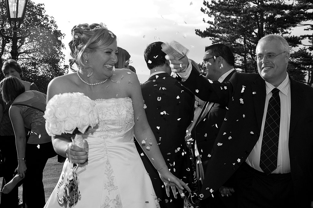 A guest surprises the Bride with another handful of confetti on the terrace at Stanhill Court Hotel, Horley captured by Surrey Lane wedding photographer