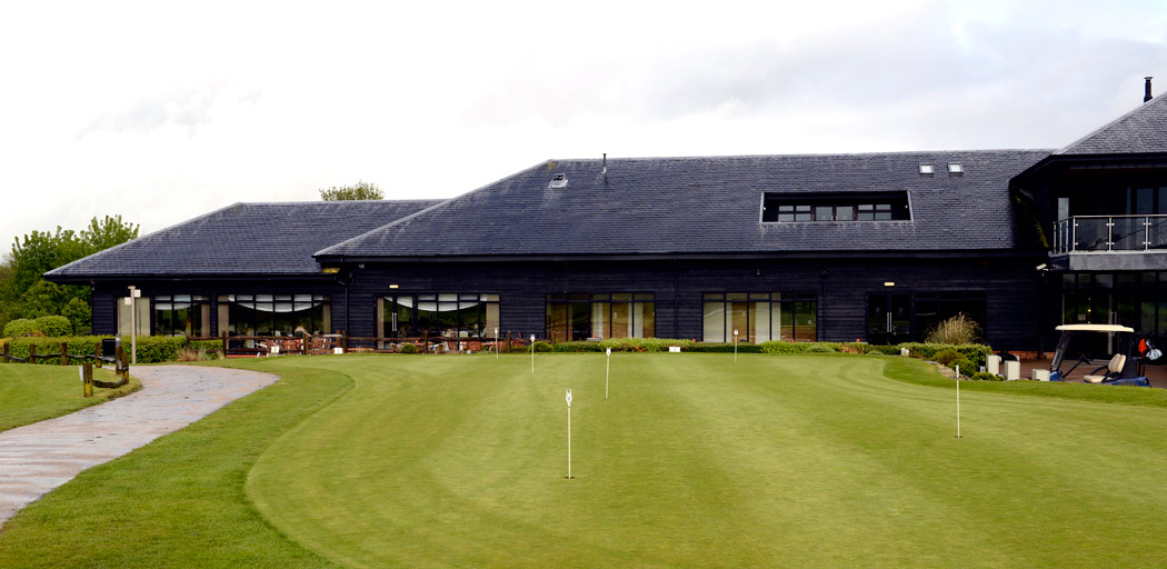 A wedding picture taken of the sleek looking black tiled and black wooden walled Surrey Downs Golf Club as captured by Surrey Lane wedding photography