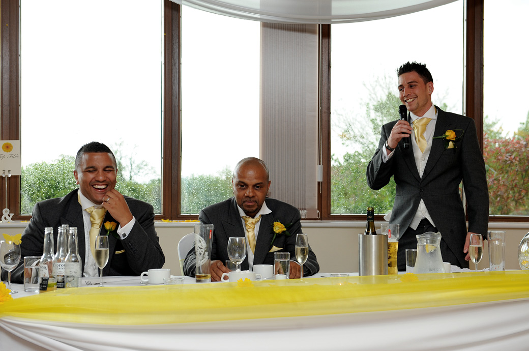 The Groom laughs during the Best Man's speech in this fun wedding picture taken at the Surrey Downs Golf Club wedding venue in the spacious Willow Suite