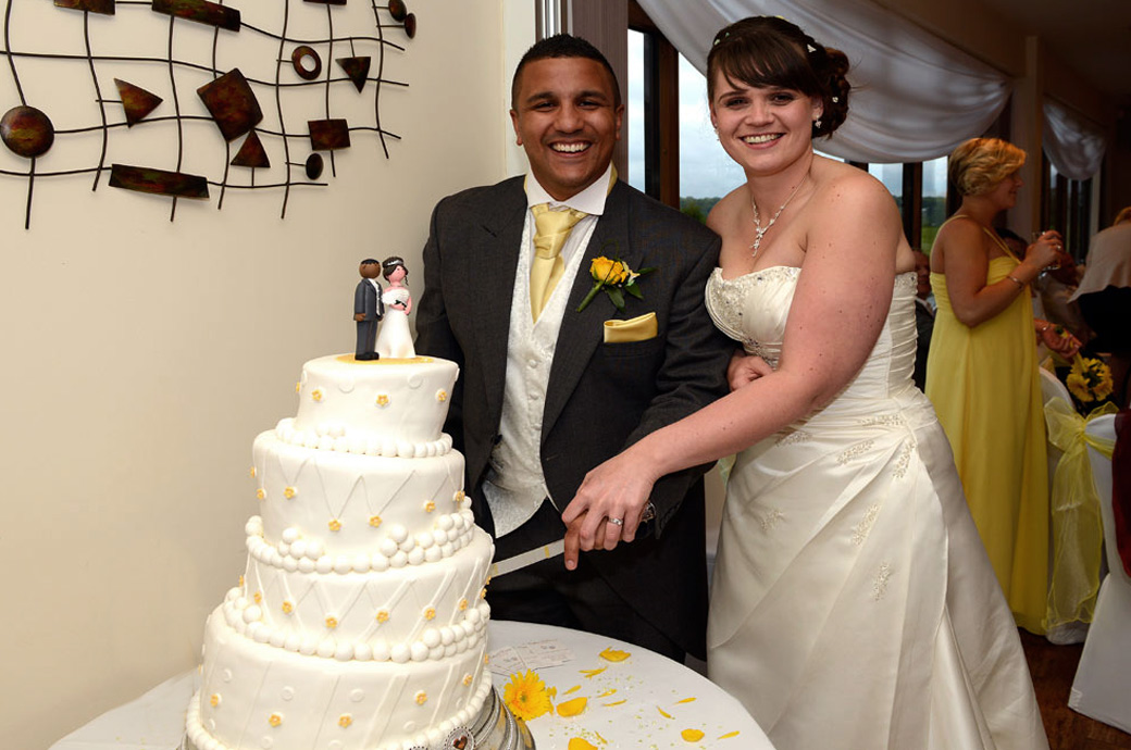 Happy newly-wed couple cutting the wedding cake wedding picture captured at Surrey Downs Golf Club in the inviting Willow Suite