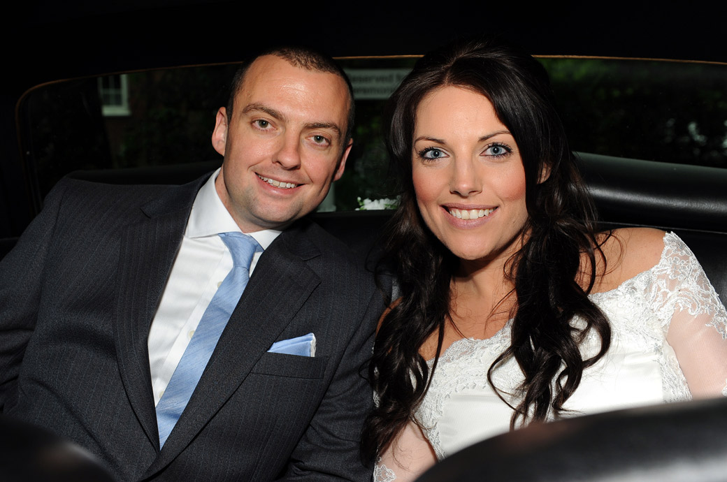 Beaming happy husband and wife smile in the back of the car in this wedding photo for the Surrey Lane wedding photographer before they leave Sutton Register Office for their reception