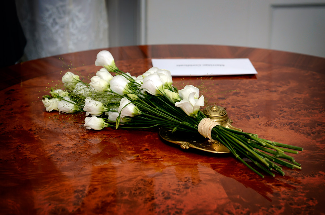 Wedding photo of the Bride's bouquet lying on the table along the marriage certificate taken at the popular and intimate Surrey wedding venue Sutton Register Office