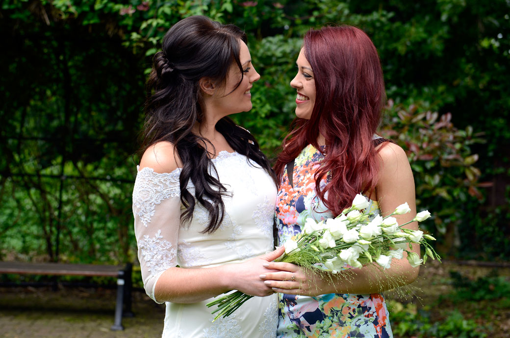 Lovely smiling intimate moment between the Bride and her sister in this wedding photo taken outside in the garden at Sutton Register Office an intimate Surrey wedding venue