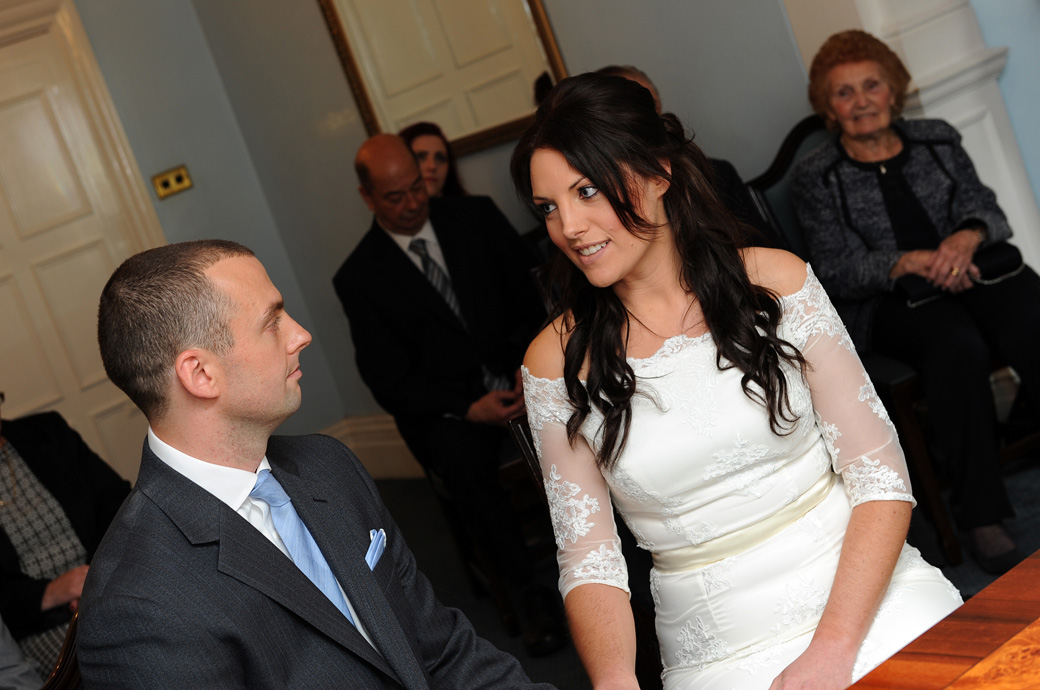 The Bride looks to her husband to be in this touching wedding photograph taken during the service at Sutton Register Office by a Surrey Lane wedding photographer