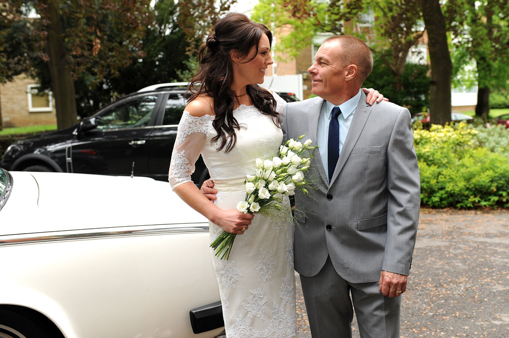 Father and Bride look to each other in this sweet and fun wedding photograph taken outside Sutton Register Office a warm,  welcoming and intimate Surrey wedding venue