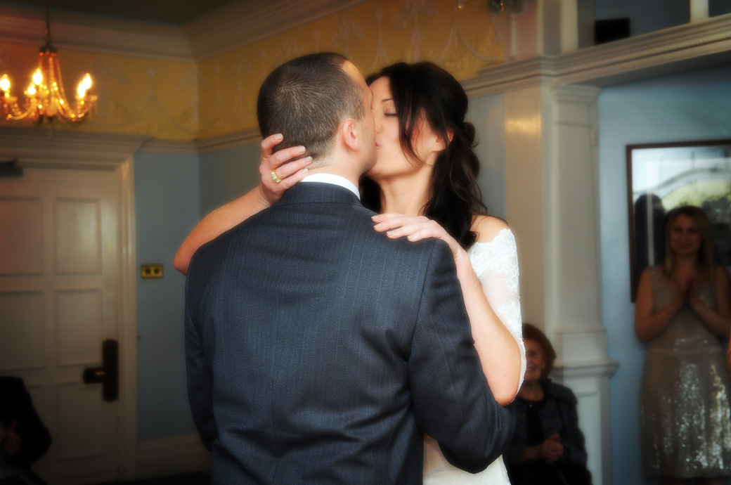 Husband and wife now passionately kiss in this soft focus wedding photo taken in the Drawing Room in Sutton Register Office by Surrey Lane wedding photographers
