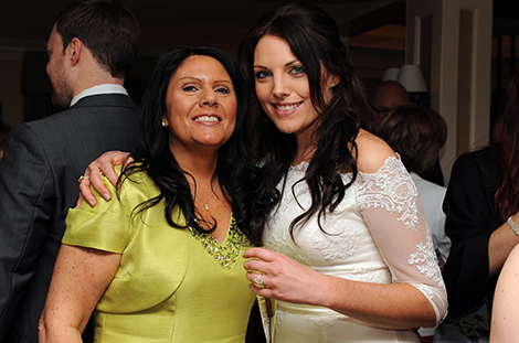 Lovely natural wedding picture of the happy Bride putting an arm around her smiling mother after her marriage at Sutton Register Office a popular wedding venue in  Surrey