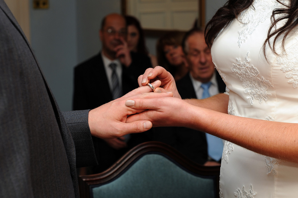 Placing the ring on her husband to be's finger in this close up wedding photograph taken in the Drawing Room at Sutton Register Office a popular wedding venue in Surrey