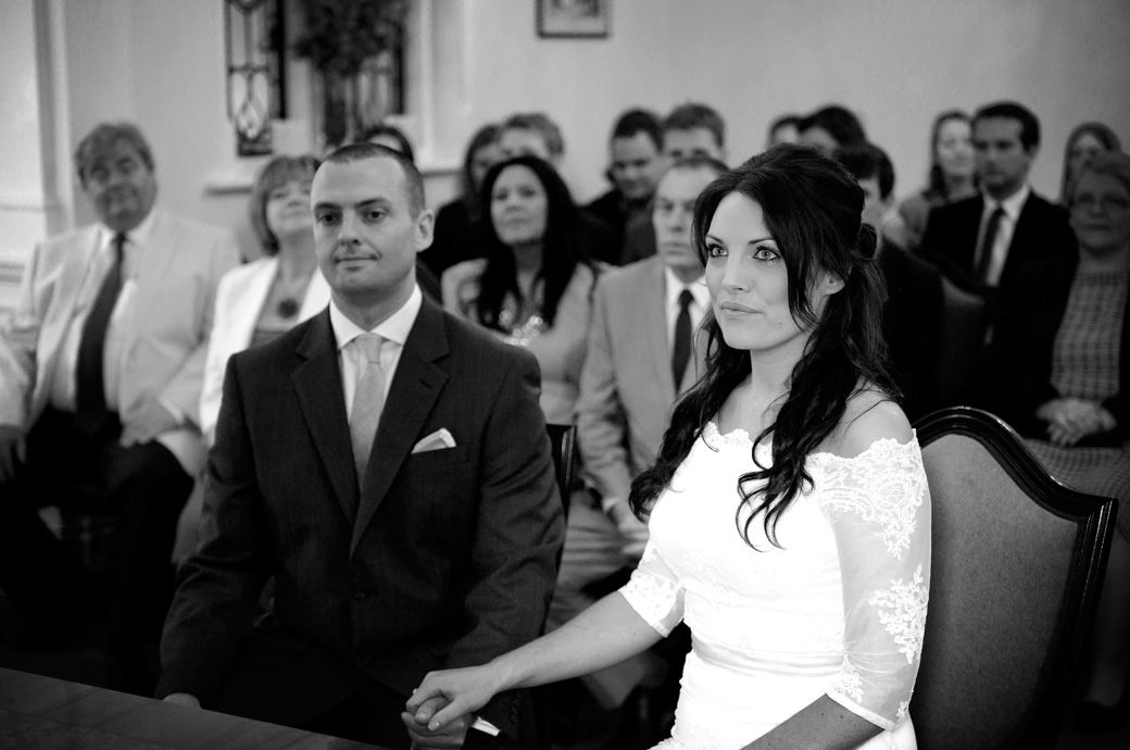 A radiant beautiful Bride captured in this lovely wedding photo as she holds the Groom's hand and listens to the registrar at Sutton Register Office a friendly wedding venue in Surrey